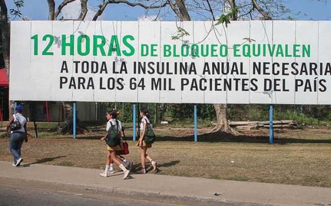 A billboard reads '12 hours of blockade are the equivalent to the annual insulin needed to treat the entire country's 64,000 patients'
