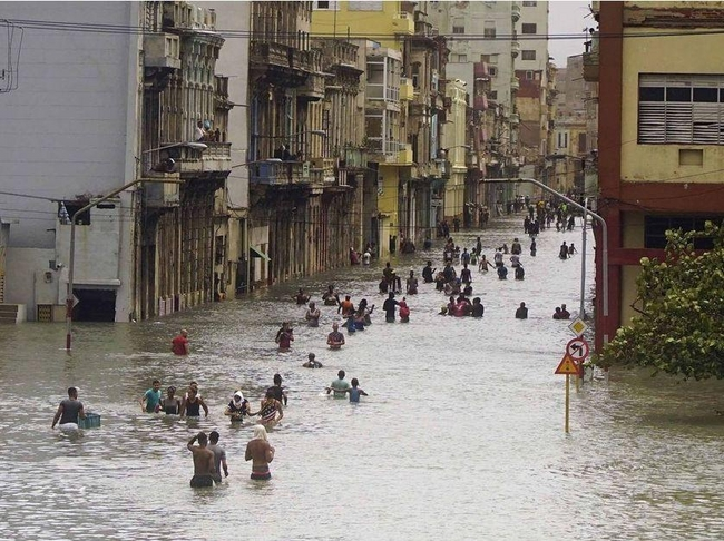 People move through flooded streets in Havana after the passage of Hurricane Irma, in Cuba, Sunday, Sept. 10, 2017