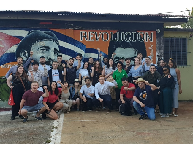 The 2019 delegation at a Julio Antonio Mella International Camp mural