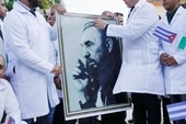 Cuban doctors hold an image of late Cuban President Fidel Castro during a farewell ceremony before departing to Italy to assist, amid concerns about the spread of the coronavirus disease (COVID-19) ou