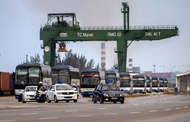 Buses escorted by police transport carry holidaymakers to an airport near Havana