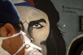 A man wearing a mask walks alongside a mural of Ernesto